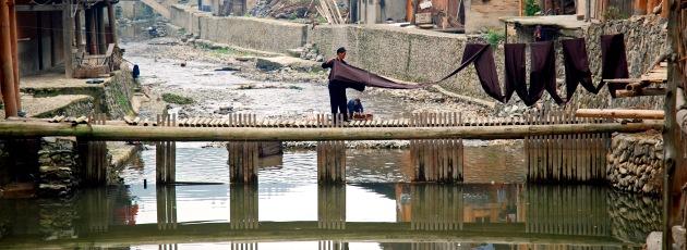 Torka tyg vid floden i Zhaoxing, Guizhou